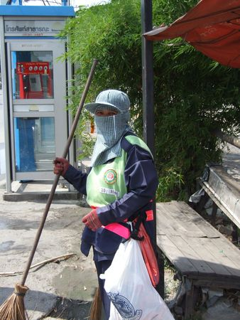 BANGKOK, THAILAND - OCTOBER 28: Thai woman road sweeper in her clothes designed to block sunlight and dust October 28, 2005 in Bangkok.