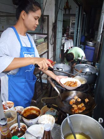 BANGKOK, THAILAND - MAY 16: Thai woman cooking food in an outdoor kitchen May 16, 2005 in Bangkok.