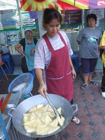 fryingpan: BANGKOK, THAILAND - MAY 18: Thai woman deep fries Thai snacks May 18, 2005 in Bangkok.