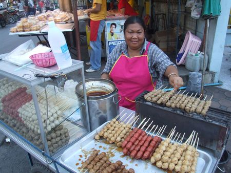 BANGKOK, THAILAND - MAY 18: Thai woman selling cooked meats on sticks May 18, 2005 in Bangkok.