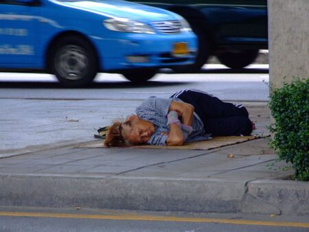 social outcast: BANGKOK, THAILAND - AUGUST 25: Thai woman sleeping on the roadside August 25, 2007 in Bangkok.