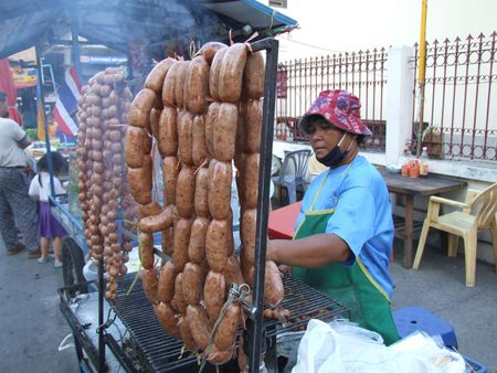 BANGKOK, THAILAND - JANUARY 6: Thai woman cooking and selling sausages on the street January 6, 2005 in Bangkok.