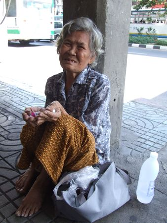 BANGKOK, THAILAND - SEPTEMBER 23 : Old lady begs for money on the side of the road in central Bangkok September 23, 2007 in Bangkok.  Stock Photo - 7492387