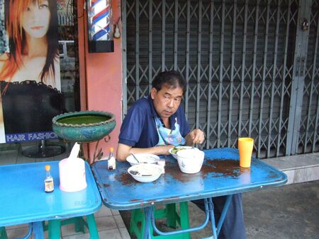 BANGKOK, THAILAND - DECEMBER 17 : Thai man eats in a restaurant on the roadside December 17, 2005 in Bangkok.