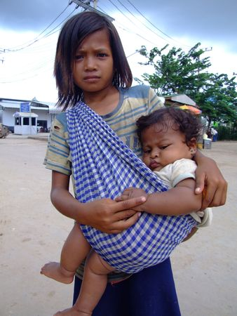CAMBODIA BORDER, THAILAND - OCTOBER 07 : Young Cambodian girl carries her sister begs for money on the Thai Cambodian border October 07, 2007 in Cambodia border, Thailand.