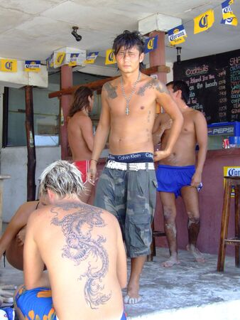 boy  naked: KOH PHANGAN, THAILAND - MARCH 22 : Tourists relax in a beach bar on Haad Rin beach March 22, 2006 in Koh Phangan.