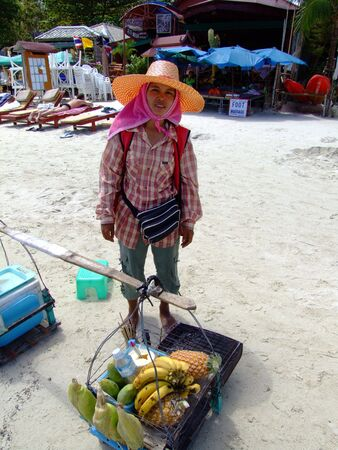 KOH SAMUI, THAILAND - JANUARY 21: Thai woman sells fruit and sweetcorn to tourists on January 21, 2005 in Koh Samui.  Stock Photo - 7492430