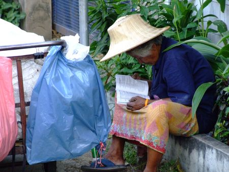 BANGKOK, THAILAND - JANUARY 28: Thai elderly woman reads a book by the road on January 28, 2006 in Bangkok.