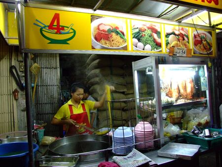 BANGKOK, THAILAND - JANUARY 29: Thai woman cooks and sells Thai noodles on January 29, 2006 in Bangkok.
