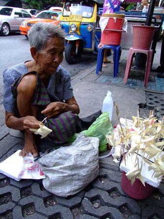 adult vietnam: BANGKOK, THAILAND - MAY 20: Thai elderly woman sells paper fish on sticks on the street on May 20, 2008 in Bangkok.  Editorial