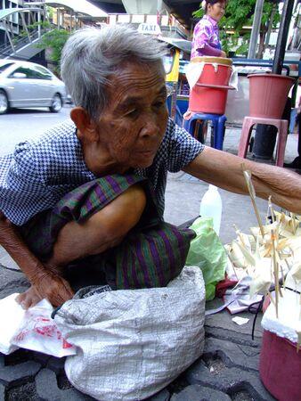 BANGKOK, THAILAND - MAY 20: Thai elderly woman sells paper fish on sticks on the street on May 20, 2008 in Bangkok.