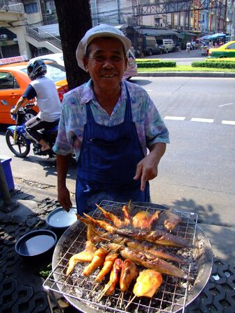 BANGKOK, THAILAND - APRIL 3: Thai man cooks and sells grilled chicken and fish on April 3, 2007 in Bangkok.  Stock Photo - 7492595