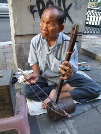 crippled: BANGKOK, THAILAND - APRIL 03: Elderly Thai blind man sits by the roadside and plays music for passing tourists and Thai people to make money. April 03 2007 in Bangkok.