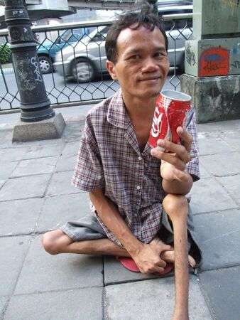 BANGKOK, THAILAND - SEPTEMBER 23: Thai crippled man sits on a path in central Bangkok begging for money with a coke can. September 23 2007 in Bangkok.