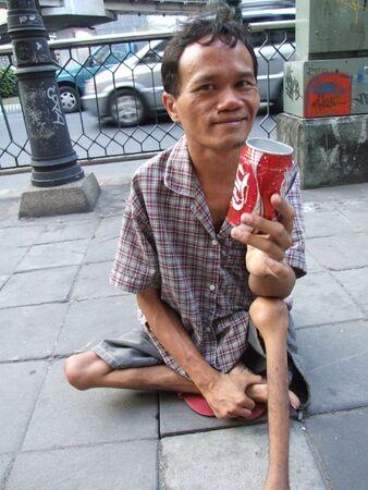 BANGKOK, THAILAND - 23 SEPTEMBER: Thaise verlamde man zit op een pad in centraal Bangkok bedelen voor geld met een cola kan. September 23 2007 in Bangkok.