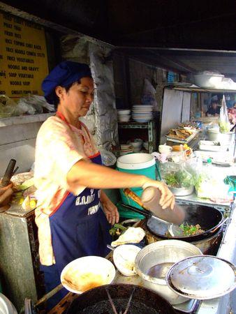fryingpan: BANGKOK, THAILAND - APRIL 3: Thai woman cooks food in an outdoor kitchen April 3, 2007 in Bangkok.  Editorial