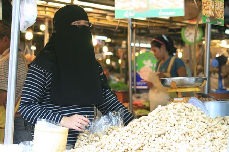 BANGKOK, THAILAND - JUNE 6: Thai Islamic woman sells peanuts in a market on June 6, 2009 in Bangkok.