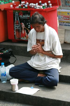 BANGKOK, THAILAND - NOVEMBER 29: Thai man sits for money by the road on November 29, 2008 in Bangkok.