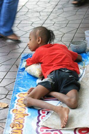 crippled: BANGKOK, THAILAND - DECEMBER 7 2008: Thai crippled boy lays on the roadside begging for money on Khaosarn road. December 7 2008 in Bangkok.
