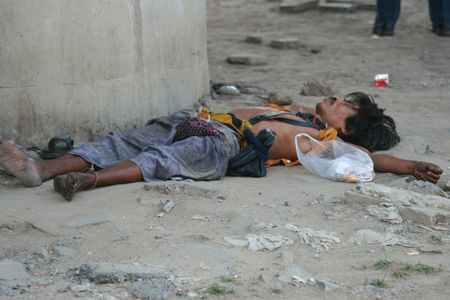 BANGKOK, THAILAND - MARCH 18: Thai homeless man sleeps by the roadside on March 18, 2009 in Bangkok.