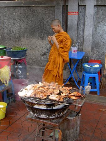 BANGKOK, THAILAND - JULY 26: Thai Buddhist monk stands behind a barbecue on Khaosarn road. July 26 2005 in Bangkok.
