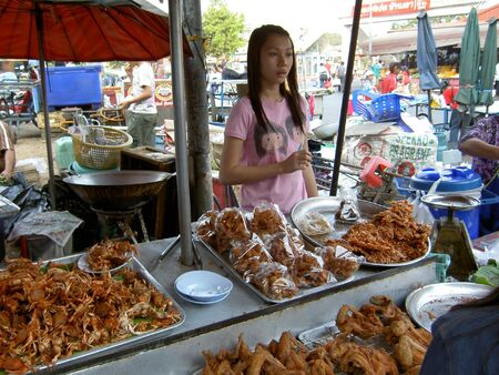 CHAING MAI, THAILAND - JUNE 22: Thai woman sells fried seafood and chicken on June 22, 2005 in Chaing Mai.