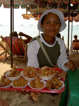 PATTAYA, THAILAND - AUGUST 25: Thai woman sells cooked fried seafood to tourists on South Pattaya beach. August 25 2005 in Pattaya.