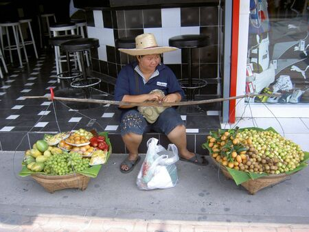 PATTAYA, THAILAND - MARCH 15: Woman sat with her baskets of fruit on March 15, 2006 in Pattaya.  Stock Photo - 7514771