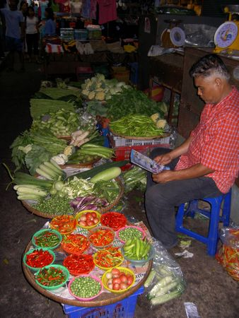 PATTAYA, THAILAND - JUNE 2: Thai man sells vegetables in a market on June 2, 2005 in Pattaya.
