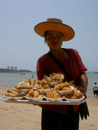 PATTAYA, THAILAND - MARCH 15: Thai woman selling deep fried seafood to tourists on South Pattaya beach on March 15, 2006 in Pattaya.
