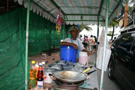 fryingpan: PATTAYA, THAILAND, JUNE 5: Thai man sells Thai food by the roadside on June 5, 2010 in Pattaya.