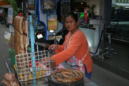 PATTAYA, THAILAND - JUNE 6: Thai woman sells Thai sausages by the street on June 6, 2010 in Pattaya.