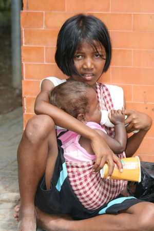 CAMBODIA - JULY 20: Child and baby sit begging for money on the roadside on July 20, 2010 in Cambodia.