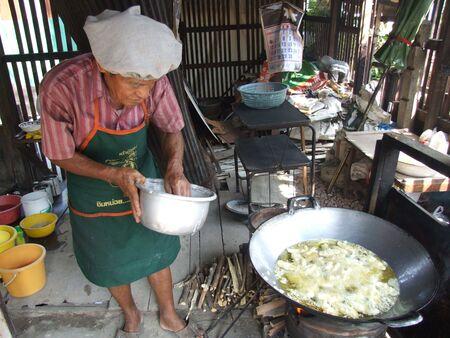fryingpan: BANGKOK, THAILAND - MAY 16: Thai man deep fries Thai snacks May 16, 2007 in Bangkok.