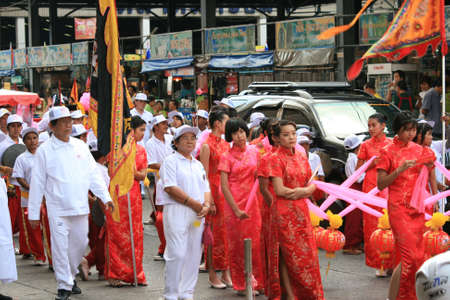 BANGKOK, THAILAND - DECEMBER 23 : Thai people dressed in red and white parade down a road in Bangkok suburbs in preparation for Chinese New Year. December 23, 2009 in Bangkok.