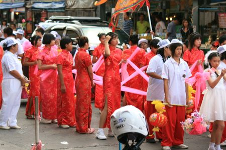 BANGKOK, THAILAND - DECEMBER 23 : Thai people dressed in red and white parade down a road in Bangkok suburbs in preparation for Chinese New Year. December 23, 2009 in Bangkok.  Stock Photo - 7525149