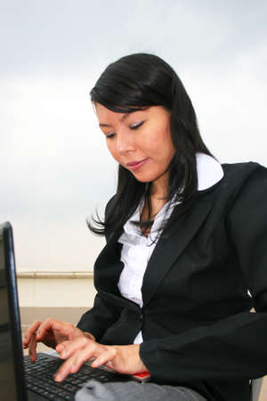 Asian business woman outdoors on a laptop. Stock Photo - 8490717