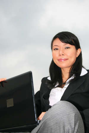 Asian business woman outdoors on a laptop. Stock Photo - 8490749