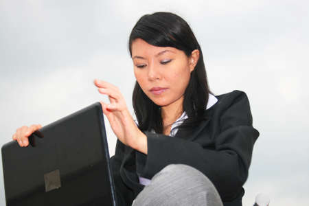 Asian business woman outdoors on a laptop. Stock Photo - 8490709