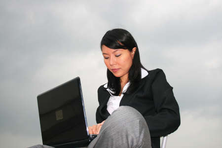 Asian business woman outdoors on a laptop. photo