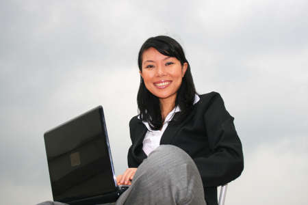 Asian business woman outdoors on a laptop. Stock Photo - 8490708