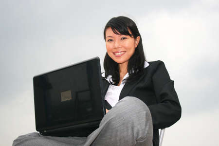 Asian business woman outdoors on a laptop. Stock Photo - 8490719