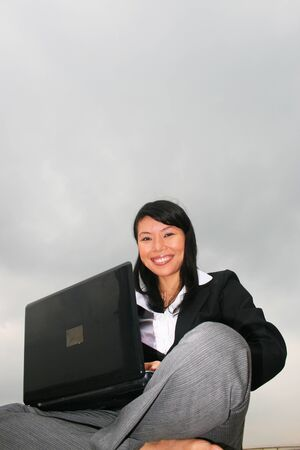 Asian business woman outdoors on a laptop. Stock Photo - 8490745