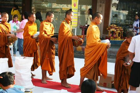 thai culture: BANGKOK - DECEMBER 5: Buddhist monks walk collecting alms in the morning on the kings birthday on December 5, 2010 in Bangkok, Thailand.