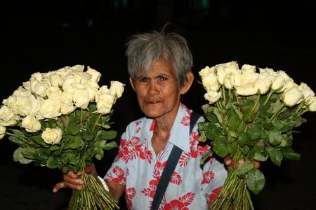 PATTAYA, THAILAND - JUNE 5: Thai elderly lady sells white roses to tourists on walking street in South Pattaya on June 5, 2010 in Pattaya.