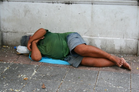 BANGKOK - SEPTEMBER 27: Thai man sleeps by the roadside on September 27, 2010 in Bangkok.