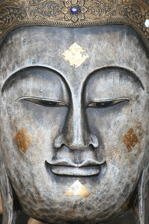 Metal Buddha face ornament, Bangkok, Thailand.  photo