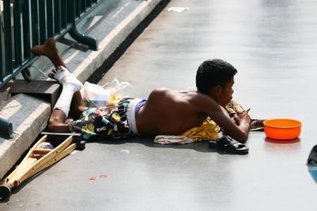crippled: BANGKOK - JANUARY 10: Thai crippled man begs for money on a bridge on January 10, 2010 in Bangkok, Thailand.  Editorial