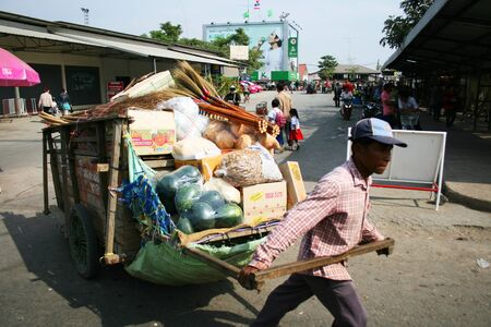 third wheel: POI PET, THAILAND - 19 JANUARY: Thai man pulls a cart near the Cambodia border crossing on January 19, 2010 in Poi Pet, Thailand.