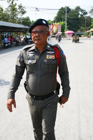 POI PET, THAILAND - 19 JANUARY: Thai police man walks down the road near the Cambodia border crossing on January 19, 2010 in Poi Pet, Thailand.